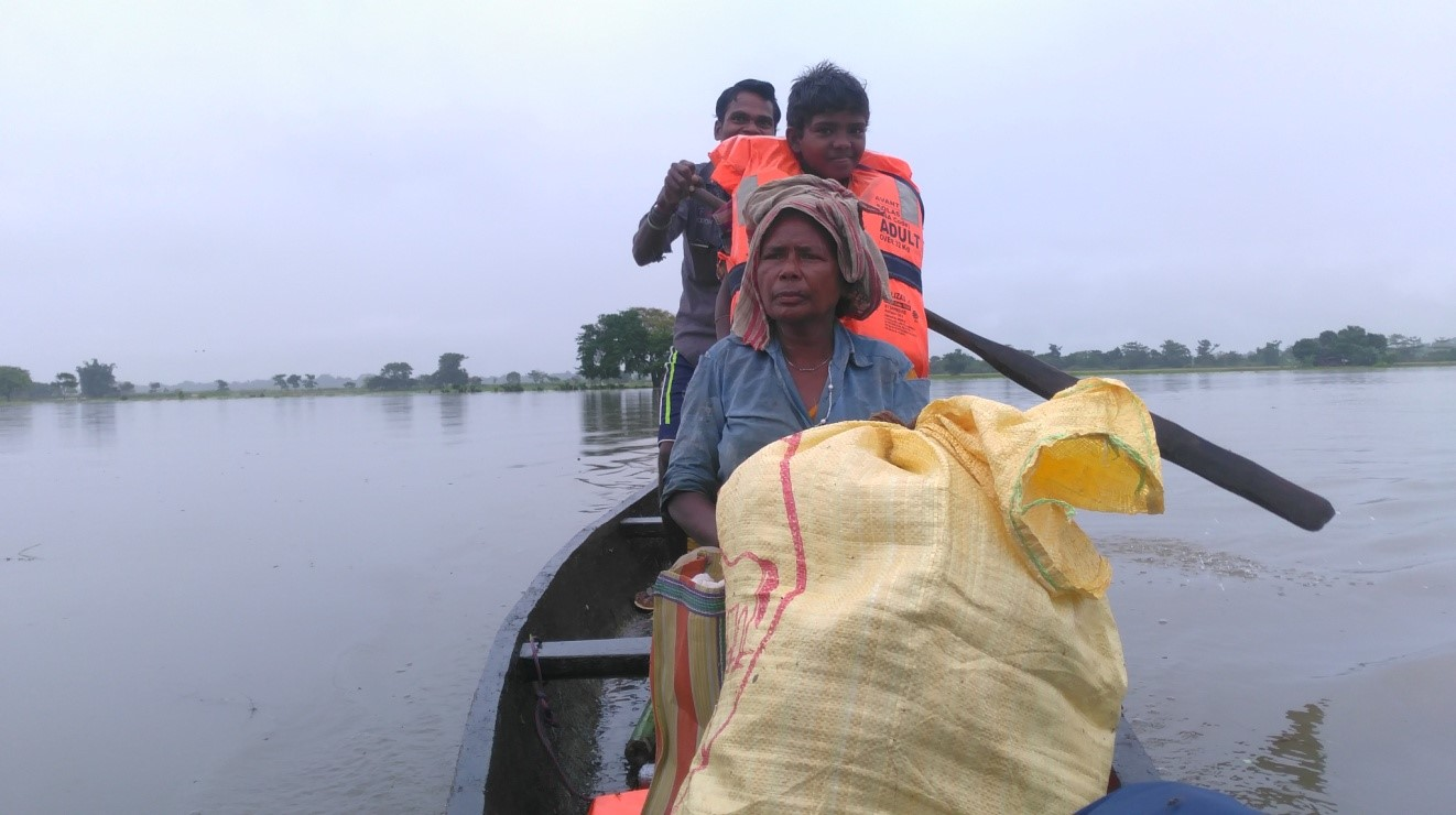 Image 8: A family stranded in a flooded village being transported to a safer location in TCF's boat.